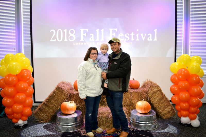 Patrick Cousins holding his daughter, standing with a young woman near pumpkins and hay. 2018 Fall Festival
