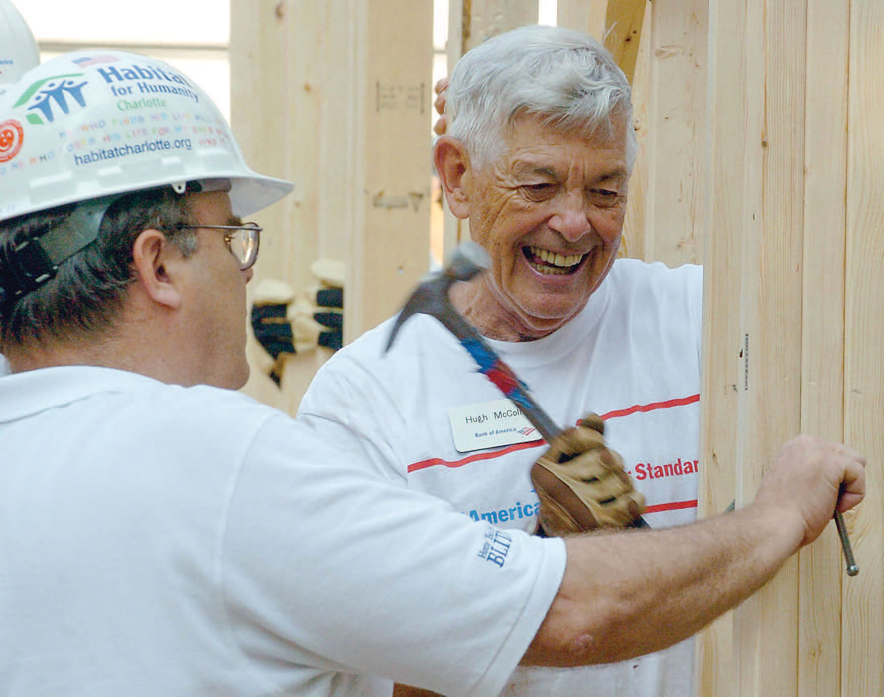 Hugh McColl standing with another man, the Habitat for Humanity Executive Director, hammering a nail into plywood.