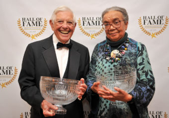 Hugh standing next to Marian, each holding a large glass Hall of Fame award.