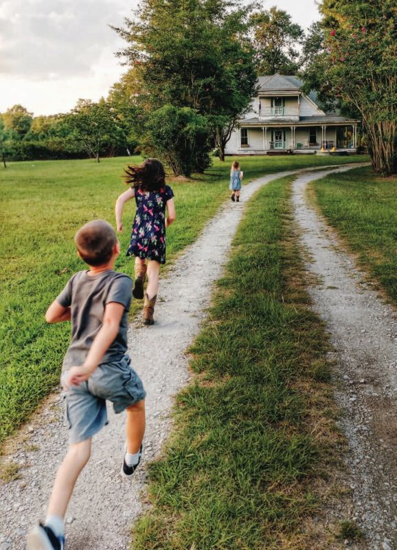 kids running to white farmhouse