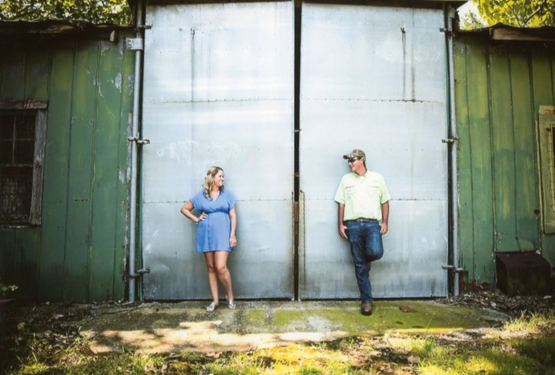 Patrick Cousins with his wife standing in front of large barn doors outside