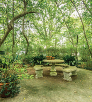 A stone table with benches surrounded by trees.